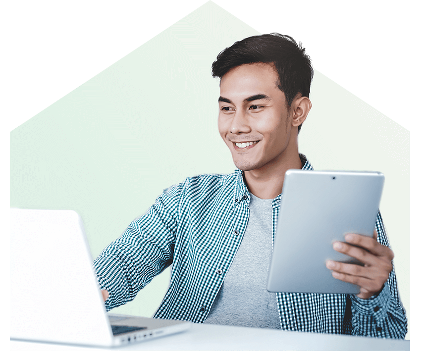 Asian man sitting in front of laptop smiling with tablet in hand